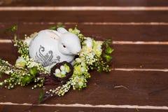 Pasen-kroon met konijntje, bloemen en eieren op een houten achtergrond Stock Fotografie