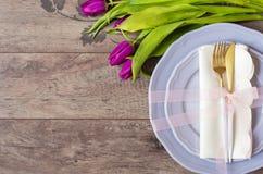 Pasen-lijst flatlay plaatsen, - huwelijkspartij, gebeurtenisdecoratie Purpere schotels en een gouden vork en een lepel op een hou stock foto's