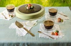 Pasen-lijst met de kaastaart van theematcha en zwarte koffie op achtergrond van groen gras royalty-vrije stock foto