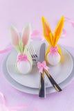 Pasen-lijst met eieren in konijntjesservetten dat wordt geplaatst Stock Foto's
