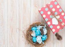 Pasen met blauwe en witte eieren in nest en giftdoos Stock Fotografie