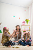 Pasen - Moeder en twee eieren geworpen van de dochterschocolade Stock Foto
