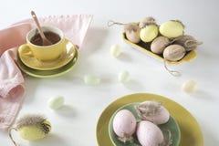 Pasen-ochtendscène in pastelkleuren, met thee en roze en gele eieren stock fotografie