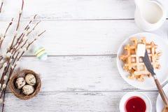 Pasen-ontbijt met kwartelseieren, wafels, fruitjam, melk en sandwiches, met wilgentak op een witte houten achtergrond Stock Foto's