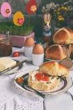 Pasen-ontbijt met traditioneel heet dwarsbroodjes, jam, boter en ei Vakantie stilleven Feestelijke lijstplaats het plaatsen decor stock foto