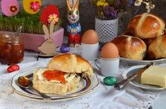 Pasen-ontbijt met traditioneel heet dwarsbroodjes, jam, boter en ei Vakantie stilleven Feestelijke lijstplaats het plaatsen decor royalty-vrije stock fotografie
