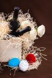 Pasen toe twee nam de de eierendoos van de flessenwijnstok lade de houten blauwe witte rode strosplinters de weinig gele Nederlan stock foto's