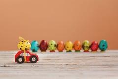 Pasen-vakantieconcept - Rode stuk speelgoed auto die geel ei dragen stock foto's