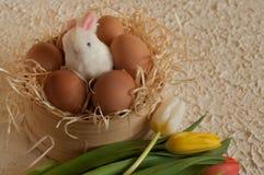 Pasen-vakantiemand met eieren, bloemen en Pasen-konijntje op rustieke houten Royalty-vrije Stock Afbeeldingen
