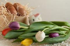Pasen-vakantiemand met eieren, bloemen en Pasen-konijntje op rustieke houten Royalty-vrije Stock Foto's
