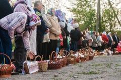 In Pasen vele mensen die zich op een rij met manden en kaarsen bevinden Stock Afbeeldingen
