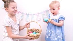 Pasen-viering: Het meisje behandelt haar jongere zuster met geschilderde paaseieren van een rieten mand royalty-vrije stock foto's