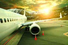 Pasenger飞行在机场的停车处runnway反对美丽的太阳 免版税库存图片