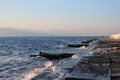 paseo al mar a lo largo del embarcadero de la ciudad en una mañana escarchada del invierno fotos de archivo