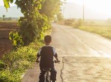 Paseo asiático lindo del muchacho una bicicleta en el camino local Imagen de archivo libre de regalías