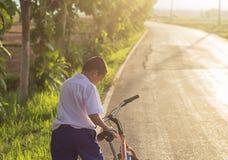 Paseo asiático lindo del muchacho una bicicleta en el camino local Imagen de archivo