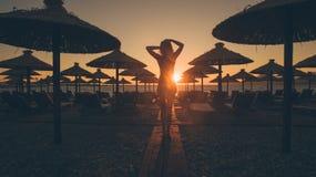 Paseo atractivo de la mujer en la playa en la puesta del sol Fotografía de archivo libre de regalías