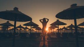 Paseo atractivo de la mujer en la playa en la puesta del sol Fotografía de archivo