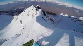 Paseo backcountry del Snowboarder del top de la montaña nevosa peligroso extremo almacen de metraje de vídeo