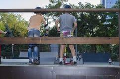 Paseo de dos adolescentes en la vespa del retroceso por el skatepark Foto de archivo