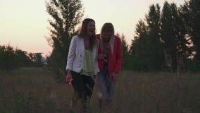 Paseo de dos muchachas en el fild en puesta del sol almacen de video