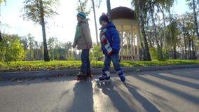 Paseo de dos niños pequeños en parque del otoño en los rodillos almacen de metraje de vídeo