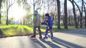 Paseo de dos niños pequeños en parque del otoño en rollerblades metrajes