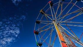 Paseo de Ferris Wheel/del parque de atracciones con el cielo azul profundo Fotografía de archivo libre de regalías