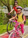 Paseo de la bici de la familia Casco de la bicicleta de la familia que lleva con la mochila Fotos de archivo