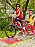 Paseo de la bici de la familia Casco de la bicicleta de la familia que lleva con la mochila Foto de archivo