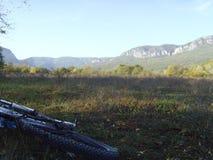 Paseo de la bici en terreno de la montaña La bici miente en la hierba en un área montañosa Imagen de archivo libre de regalías