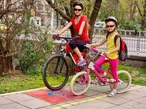 Paseo de la bici de la familia Casco de la bicicleta de la familia que lleva con la mochila Imágenes de archivo libres de regalías