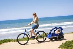 Paseo de la bicicleta de la familia a lo largo de la playa Imágenes de archivo libres de regalías