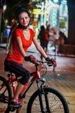 Paseo de la bicicleta de la noche de la ciudad Muchachas que llevan el casco de la bicicleta Imagen de archivo