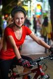 Paseo de la bicicleta de la noche de la ciudad Muchachas que llevan el casco de la bicicleta Imágenes de archivo libres de regalías