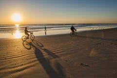Paseo de la bicicleta en la salida del sol en la playa del cacao Imagen de archivo libre de regalías