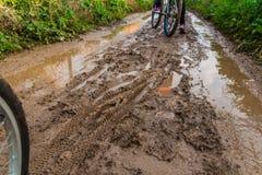 Paseo de la bicicleta a través del camino de tierra fangoso Imagen de archivo libre de regalías