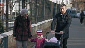 Paseo de la familia en el parque a pie con un cochecito con un niño y un niño de los años 3-4 Concepto de familia Al aire libre c metrajes
