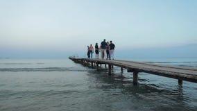 Paseo de la gente en el embarcadero al mar El caminar de la gente de la silueta almacen de metraje de vídeo
