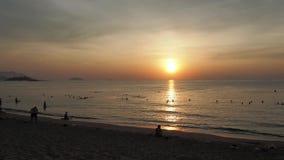 Paseo de la gente en la playa en el amanecer metrajes
