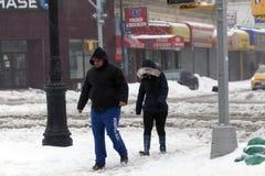 Paseo de la gente a lo largo de la calle durante tormenta de la nieve Foto de archivo libre de regalías