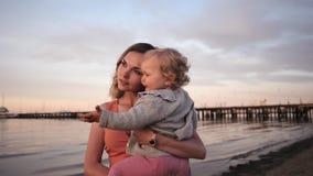 Paseo de la mamá y de la hija a lo largo de la costa en la risa de la puesta del sol almacen de video