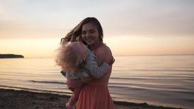 Paseo de la mamá y de la hija a lo largo de la costa en la risa de la puesta del sol almacen de metraje de vídeo