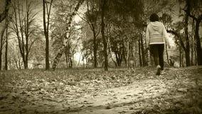 Paseo de la muchacha alrededor con el perrito del beagle en película vieja del parque otoñal almacen de metraje de vídeo