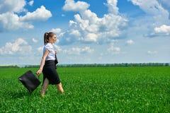 Paseo de la mujer de negocios en el campo de hierba verde al aire libre La chica joven hermosa se vistió en el traje, paisaje de  Imagen de archivo