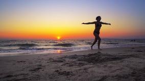 Paseo de la mujer del modelo de moda en el agua de la puesta del sol del océano con las manos abiertas de par en par Fotografía de archivo libre de regalías