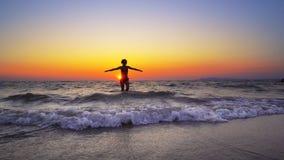 Paseo de la mujer del modelo de moda fuera del agua de la puesta del sol del océano con las manos anchas Imagen de archivo libre de regalías