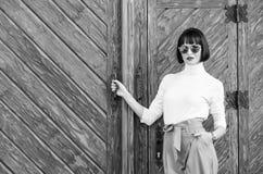 Paseo de la mujer en equipo elegante La morenita de moda de la mujer coloca al aire libre el fondo de madera Muchacha con el maqu fotos de archivo libres de regalías