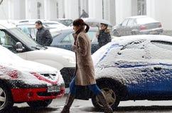 Paseo de la mujer en la caída de la nieve fotos de archivo