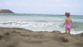 Paseo de la niña abajo de la playa en las ondas en un día hermoso metrajes